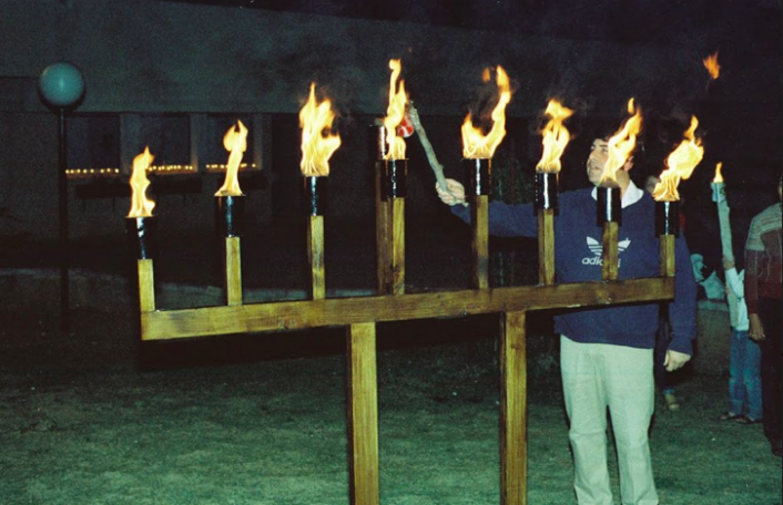 רון מנדל מדליק את החנוכיה של פריצל במרכז (כנראה 1982)