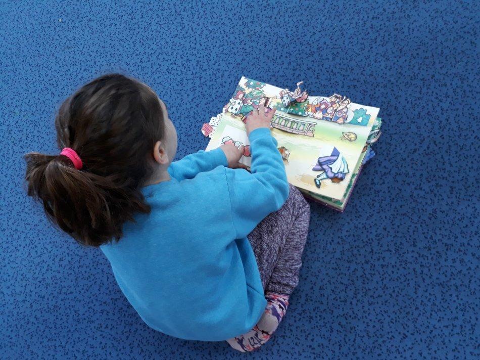 """ילדה בביה""""ס קשת קוראת בספר פופ-אפ"""